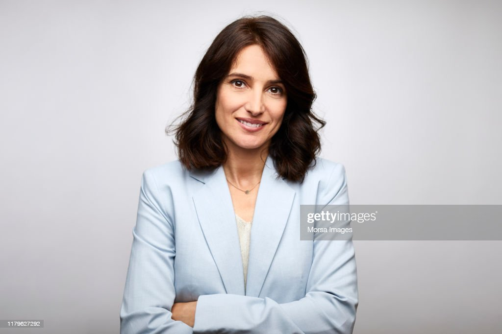 Smiling mid adult businesswoman with arms crossed : Photo