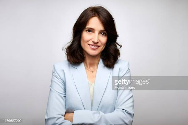 smiling mid adult businesswoman with arms crossed - diretora executiva de empresa - fotografias e filmes do acervo