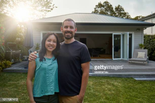 smiling mid adult couple standing against house - looking at camera stock pictures, royalty-free photos & images