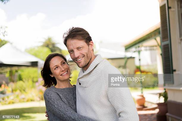 Smiling mid adult couple standing in yard