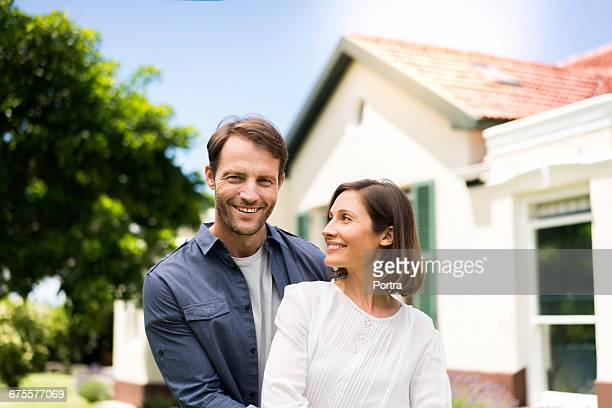 Smiling mid adult couple standing outside house