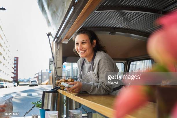 smiling mid adult female owner at food truck in city - food truck fotografías e imágenes de stock