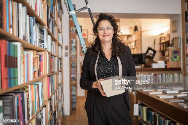 smiling mid adult female owner holding books at bookstore - book store stock photos and pictures
