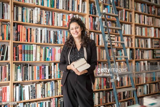 Smiling mid adult female owner standing against bookshelf with books