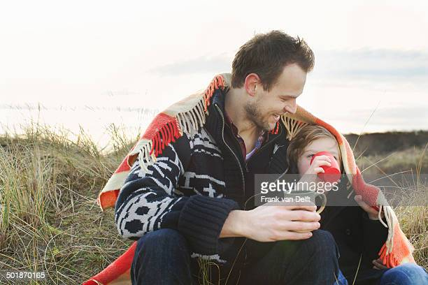 Smiling mid adult man and son wrapped in blanket on sand dunes