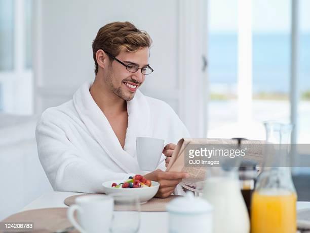 Lächelnd Mann mittleren Alters Essen Frühstück und Zeitung lesen