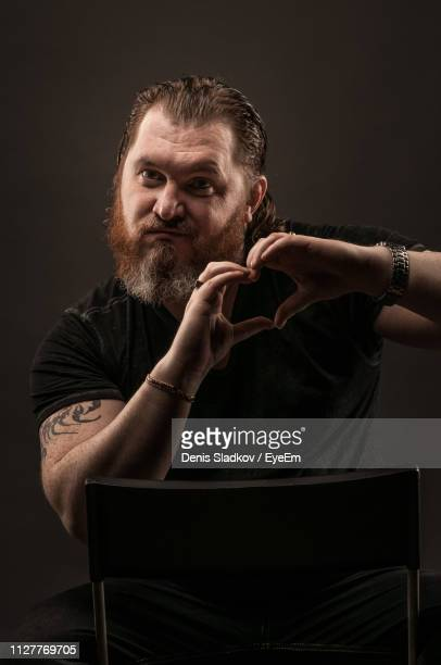 smiling mid adult man making heart shape while sitting against black background - tattoo designs hearts stock pictures, royalty-free photos & images