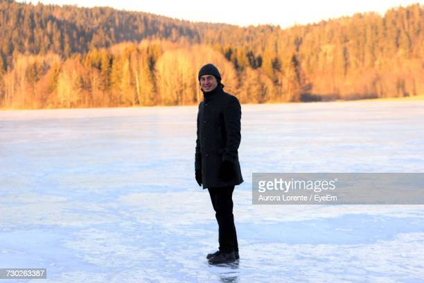 Smiling Mid Adult Man Standing On Frozen Lake Against Forest