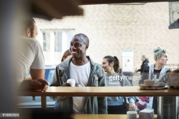 smiling mid adult man talking with male owner at food truck in city - demanding stock pictures, royalty-free photos & images