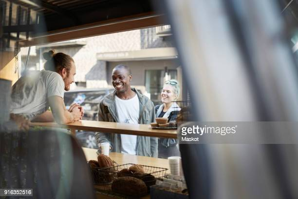 Smiling mid adult man talking with salesman at food truck