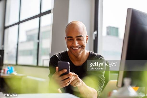 smiling mid adult man using phone at his desk - completamente calvo foto e immagini stock