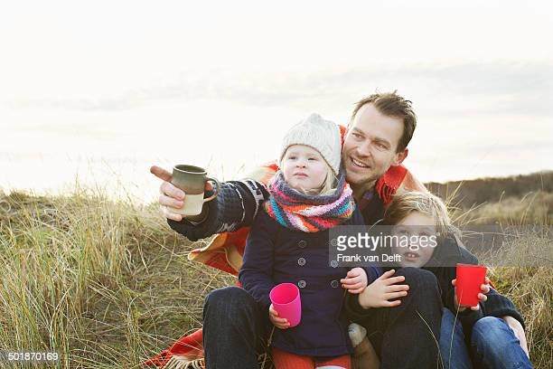 Smiling mid adult man with daughter and son on sand dunes