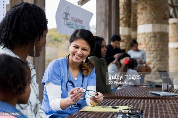 smiling mid adult optometrist offers glasses to young girl - free of charge stock pictures, royalty-free photos & images
