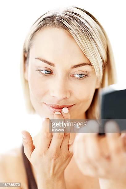 Souriant adulte jolie femme appliquant du rouge à lèvres couleur crème sur blanc