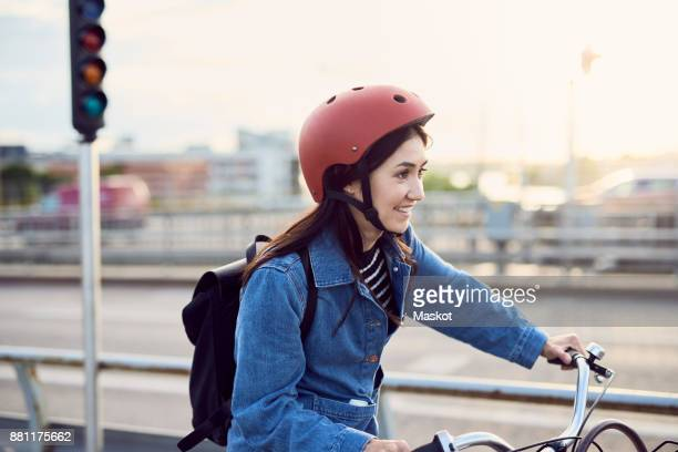 smiling mid adult woman cycling in city - sportschutzhelm stock-fotos und bilder