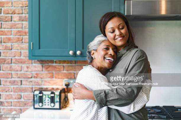 smiling mid adult woman embracing senior mother - adult offspring stock pictures, royalty-free photos & images