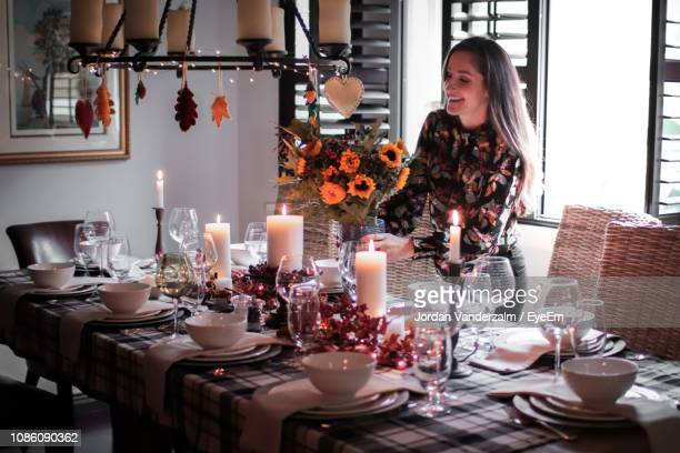 smiling mid adult woman holding arranging flower vase on dinning table at home - table decoration stock pictures, royalty-free photos & images
