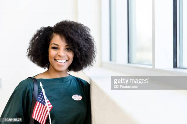 smiling mid adult woman holding flag and wearing sticker - women politics stock pictures, royalty-free photos & images