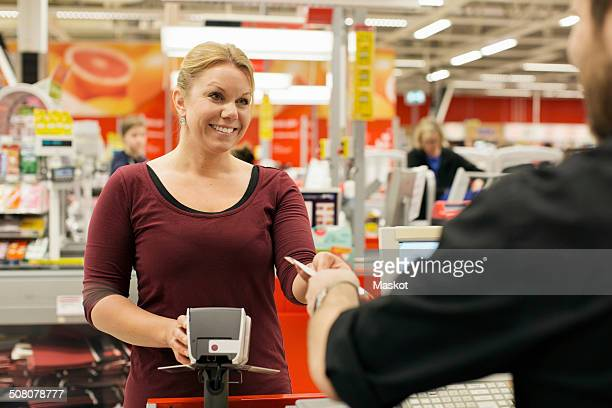 Smiling mid adult woman paying at grocery store counter