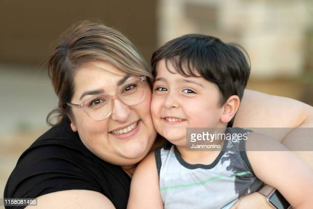 smiling mid adult woman posing with her son - stereotypically middle class stock pictures, royalty-free photos & images