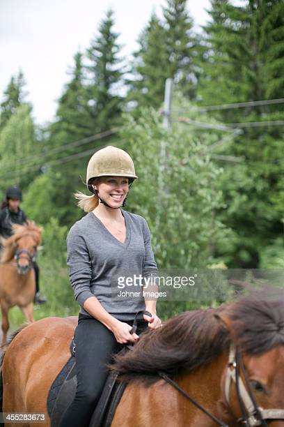 Smiling mid adult woman riding on horse