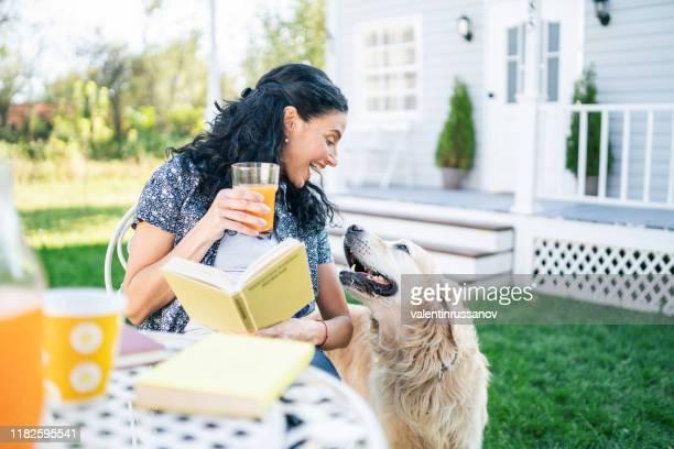 lächelnde mittlere erwachsene frau sitzt mit ihrem goldenen retriever auf dem vorgarten und liest ein buch - hairy woman stock-fotos und bilder