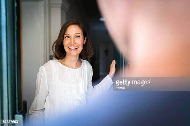 smiling mid adult woman standing on entrance - openmaken stockfoto's en -beelden