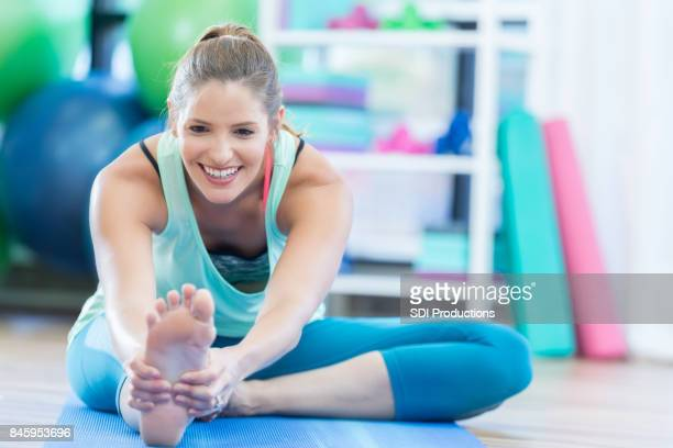 Smiling mid adult woman stretches leg on floor at local gym