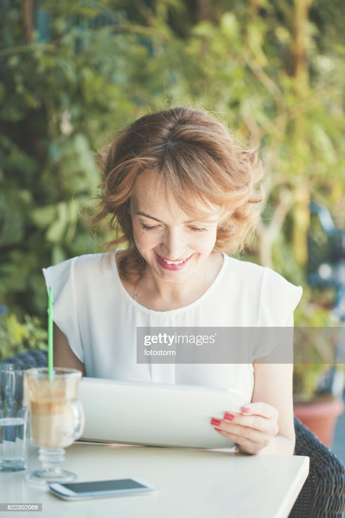 Smiling mid adult woman using digital tablet : Stock Photo