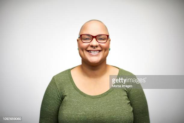 smiling mid adult woman wearing eyeglasses - bald woman stock photos and pictures