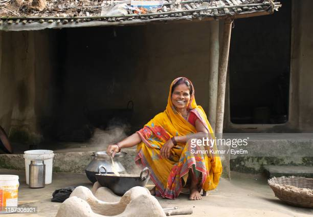 smiling mid adult woman wearing sari while cooking outside house in village - tradition fotografías e imágenes de stock