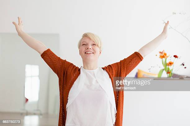 Smiling mid adult woman with arms outstretched at home