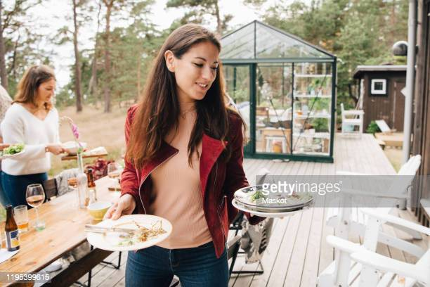smiling mid adult woman with leftovers in plate walking against dining table in patio - cleaning after party bildbanksfoton och bilder