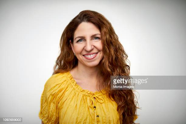 smiling mid adult woman with long wavy hair - mid volwassen stockfoto's en -beelden