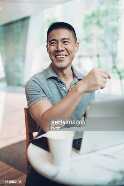 smiling middle age man with a laptop - polo shirt stock pictures, royalty-free photos & images