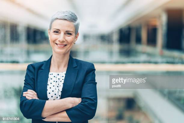 smiling middle aged businesswoman - colletti bianchi foto e immagini stock