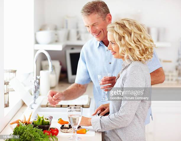 Smiling middle aged couple preparing food together at home