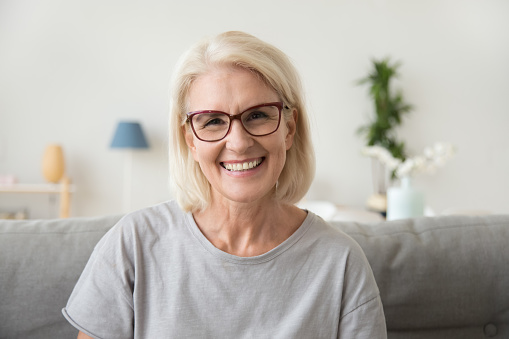 Smiling middle aged mature grey haired woman looking at camera 1080415396