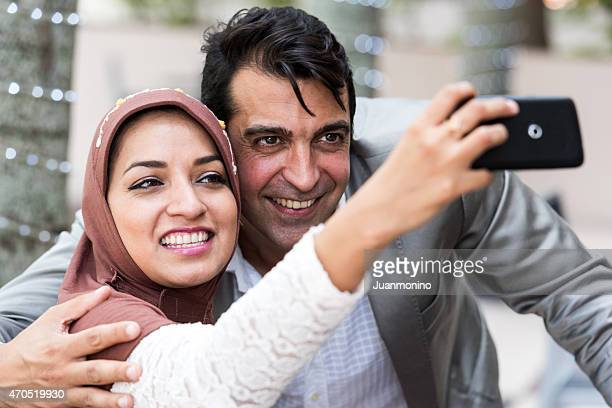 Smiling middle eastern couple taking a self photo