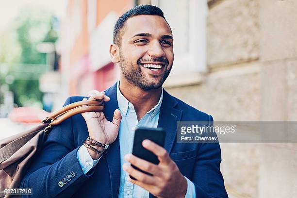 Smiling Middle Eastern ethnicity man with smart phone