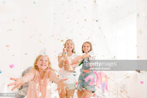 Smiling Middle Eastern girls throwing confetti in bedroom