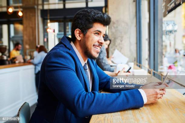 Smiling Middle Eastern man using cell phone at cafe window