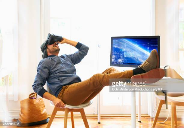 Smiling Middle Eastern man using virtual reality goggles in office