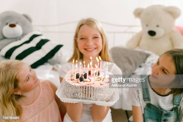 smiling middle eastern sisters with birthday cake in bedroom - happy birthday images for sister stock pictures, royalty-free photos & images