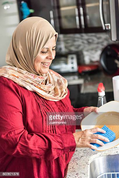 Smiling middle eastern woman washing the dishes