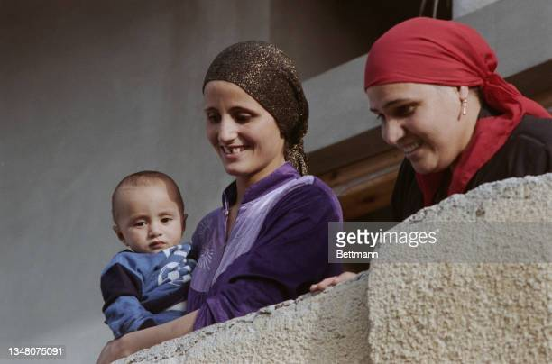 Smiling Middle Eastern women, both wearing headscarves, with one holding a baby, in Jerusalem, Israel, 1988.