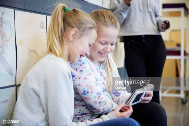 Smiling middle school girls using mobile phone in corridor
