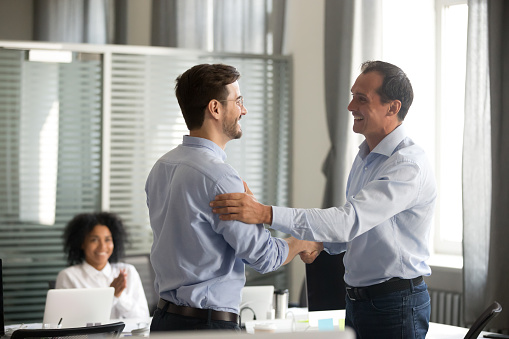 Smiling middle-aged ceo handshaking successful male worker showing respect 1070271624