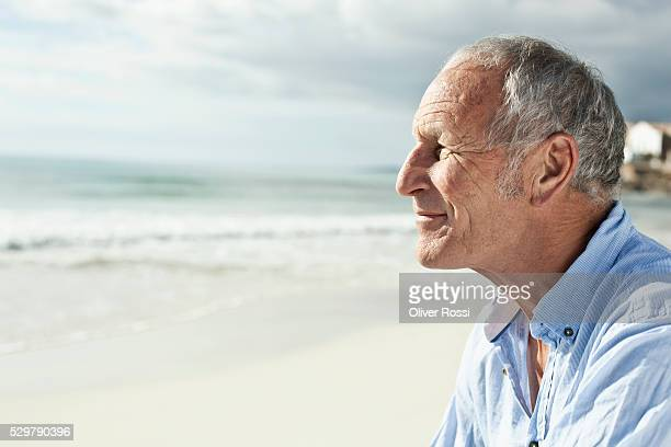 Smiling middle-aged man on beach, side view