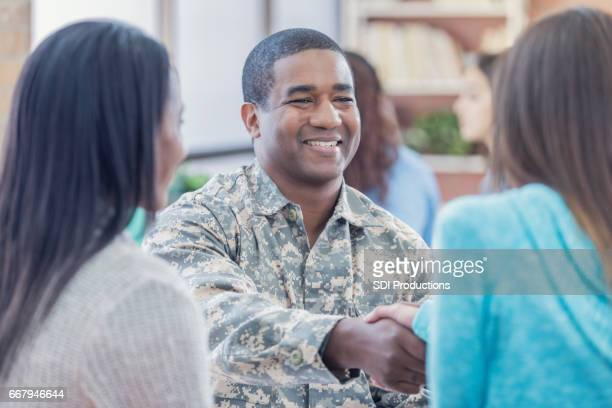 Smiling military recruiter greets students at recruitment event
